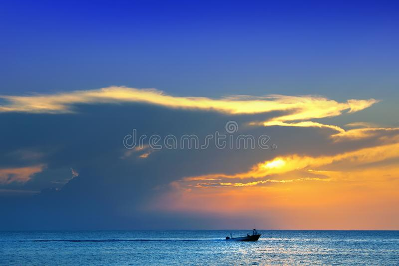 сияющие море и быстроходный катер над облачным небом и солнцем во время захода солнца в Cozumel, Мексике стоковые фото