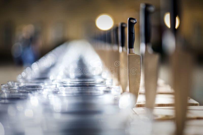 Сияющие ножи металла вставили в таблице, перспективе стоковое изображение