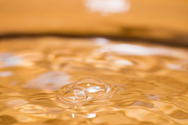 Сияющие пузыри на поверхности воды покрашенной апельсина стоковые изображения rf