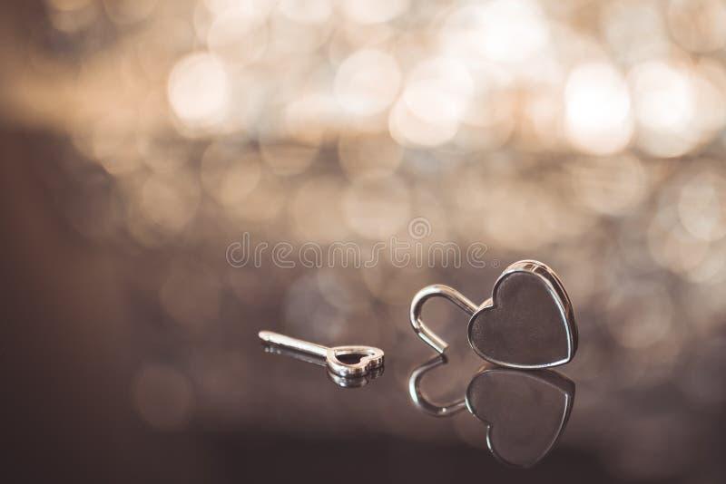 Сияющий замок и ключ сердца металла в коричневом backgrou света и bokeh стоковые изображения