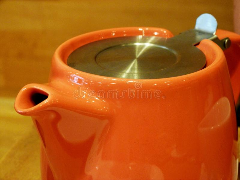 Сияющий оранжевый керамический бак чая со стальной крышкой и расплывчатой желтой предпосылкой стоковое фото