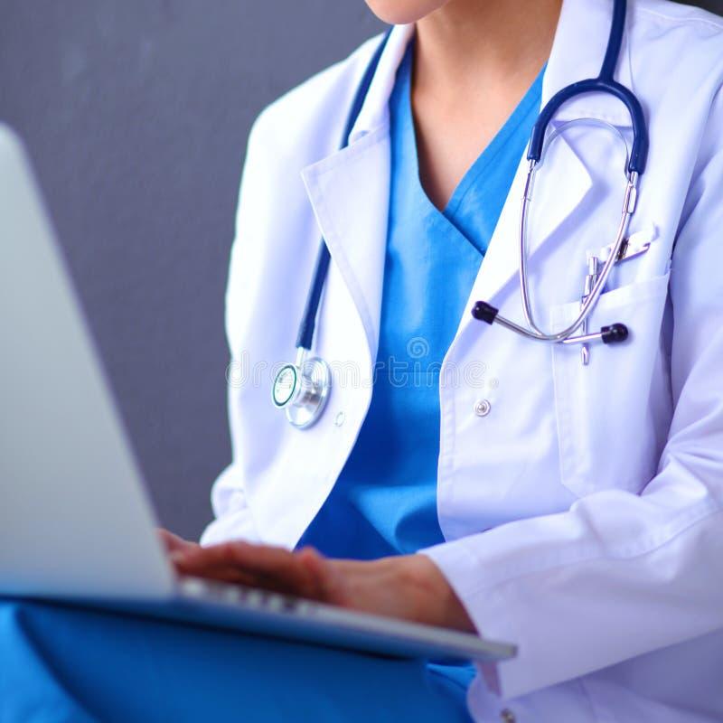 Сидеть женского доктора работая на серой предпосылке стоковая фотография rf
