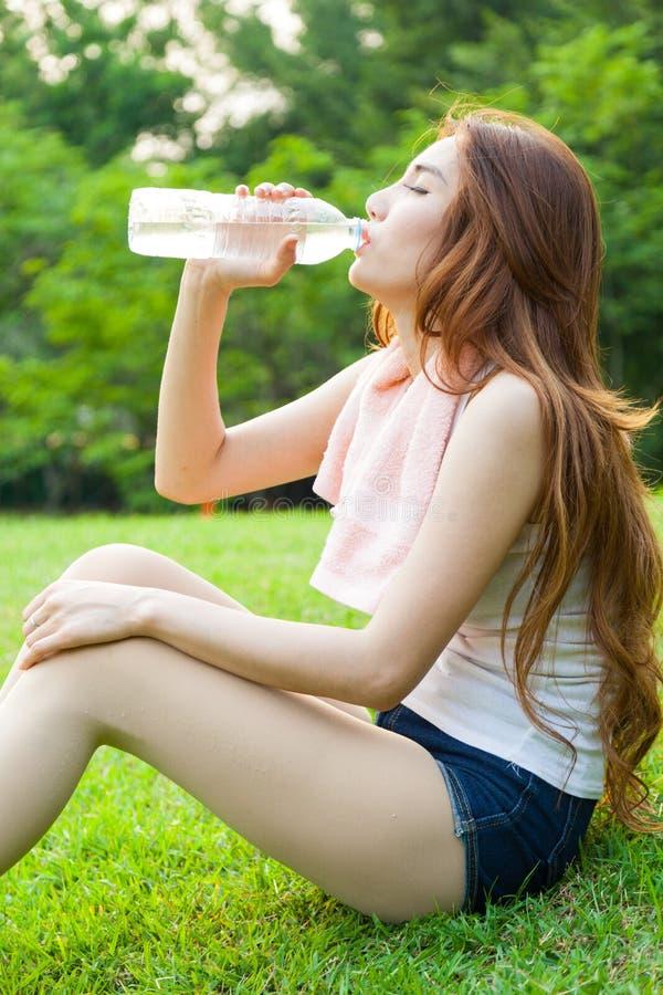 Сидеть женщины утомлянный и питьевая вода после тренировки стоковое фото