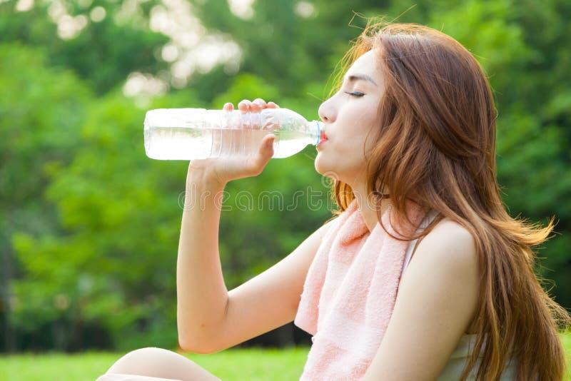 Сидеть женщины утомлянный и питьевая вода после тренировки стоковые изображения