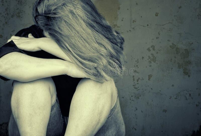 Сидеть молодой женщины плача на поле стоковое изображение