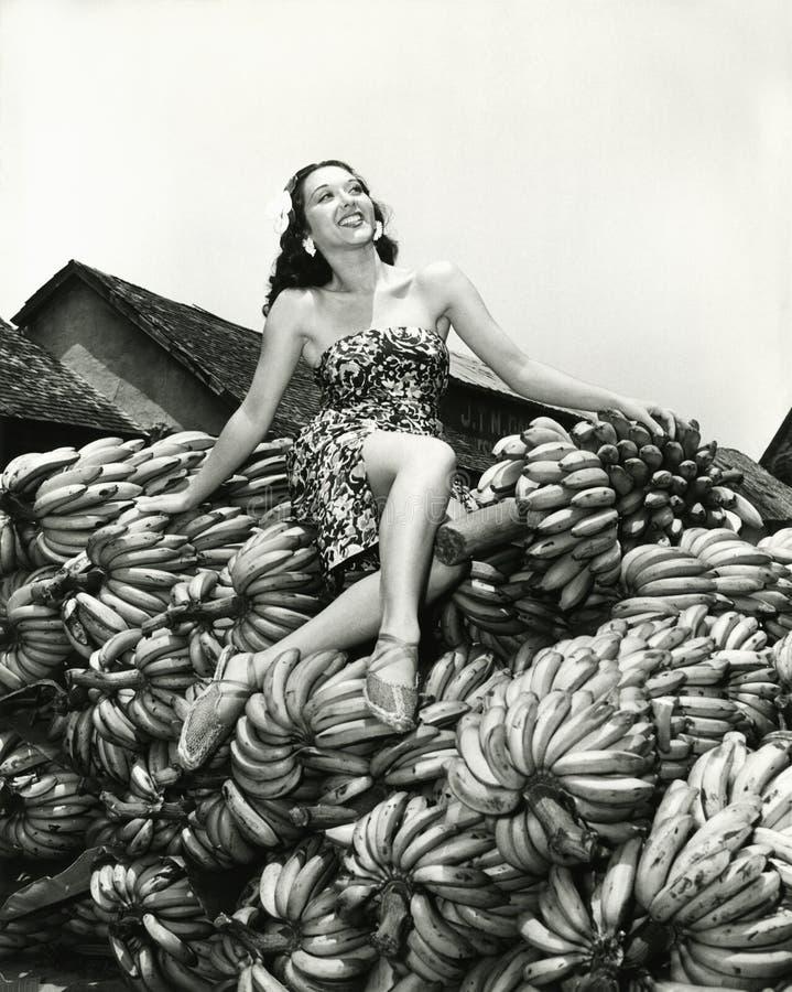 Сидеть довольно на куче бананов стоковые изображения rf
