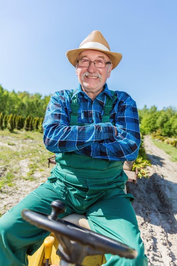 Сидеть старшего человека гордый в его тракторе после культивировать его ферму стоковые фото