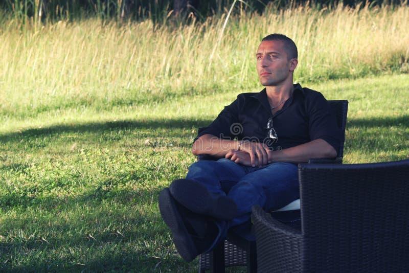 Сидеть человека ослабляя в природе запястье руки вахты релаксации карманн руки принципиальной схемы стоковое фото