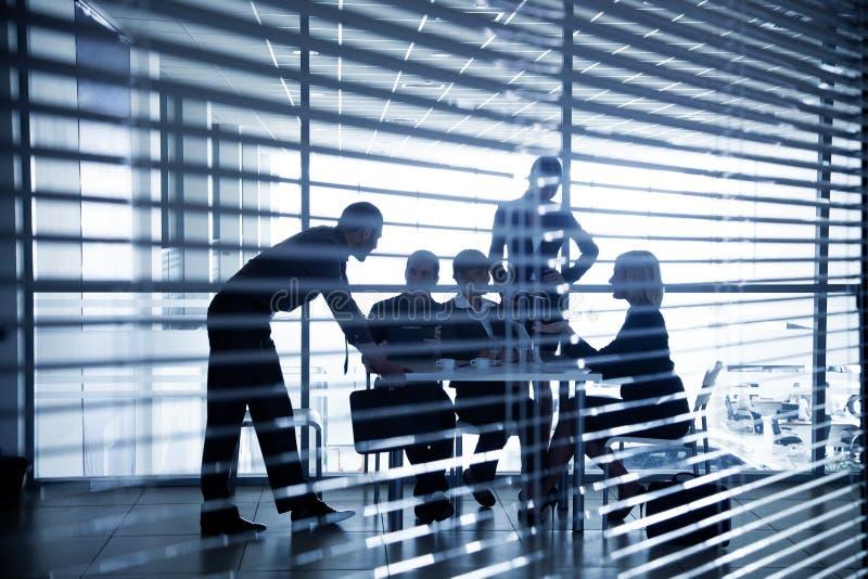 Силуэты бизнесменов через шторки стоковые изображения rf