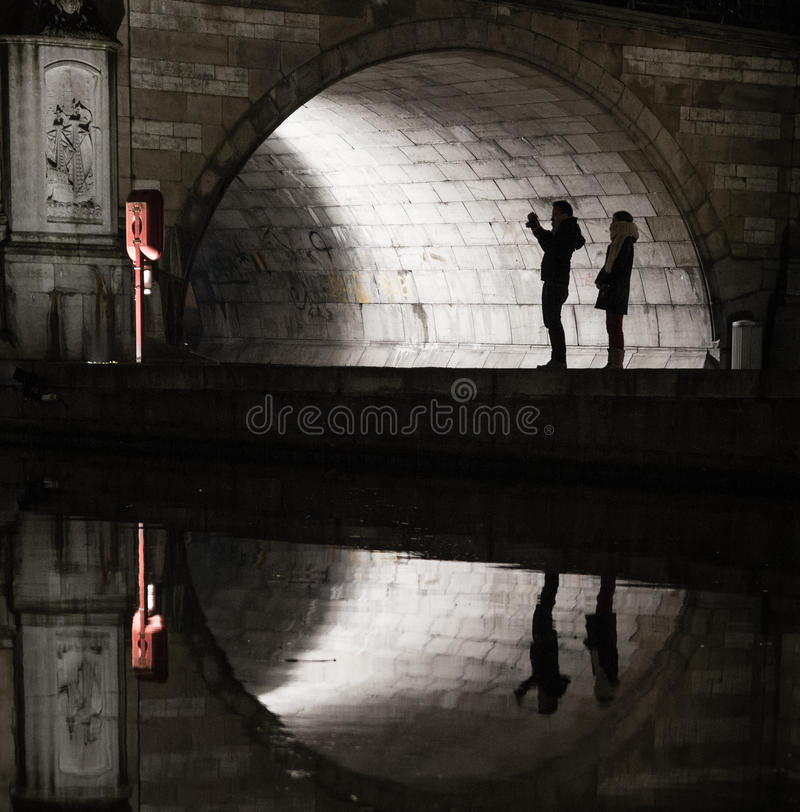 Силуэты и отражения туристов под medival мостом стоковое изображение