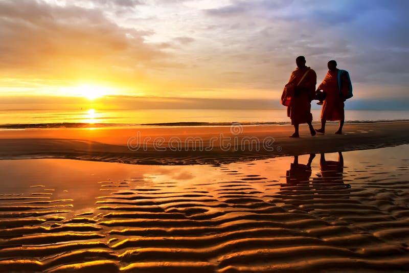 Силуэты монахов на Hua Hin приставают Таиланд к берегу стоковое фото rf