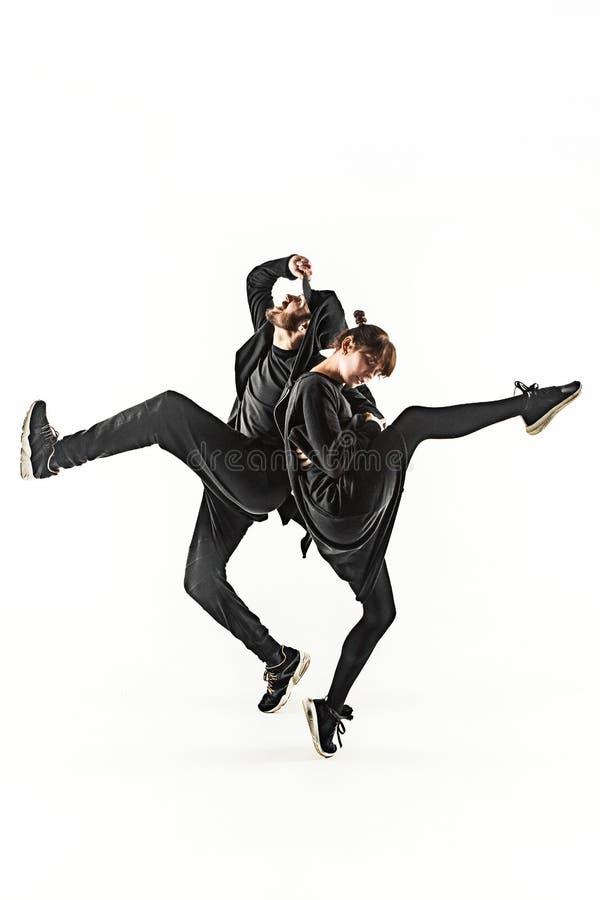 Силуэты мужчины хмеля 2 бедер и женских танцоров пролома танцуя на белой предпосылке стоковое фото