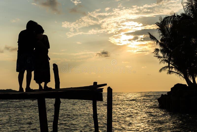 Силуэты на заходе солнца на пляже стоковое фото rf