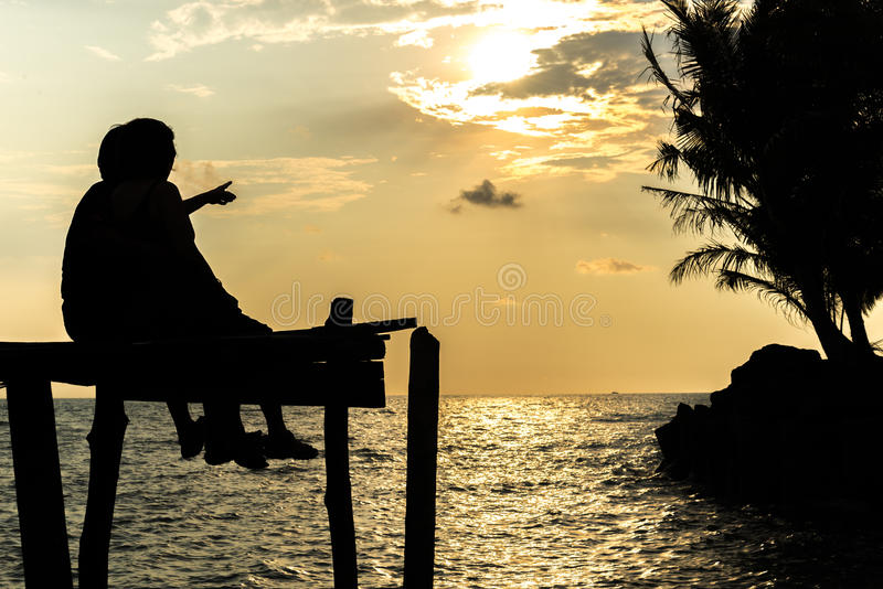 Силуэты на заходе солнца на пляже стоковые изображения