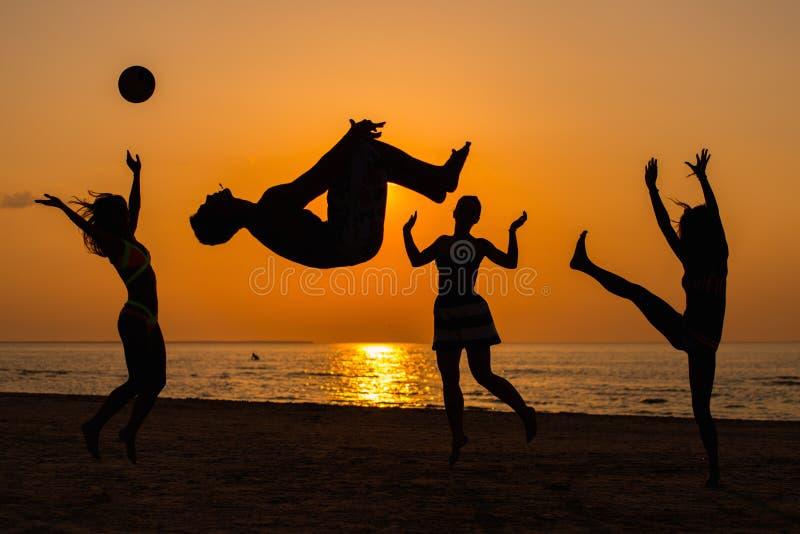 Силуэты людей имея потеху на пляже стоковое изображение
