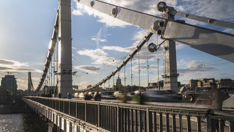 Силуэты людей и автомобилей на стальном мосте стоковая фотография