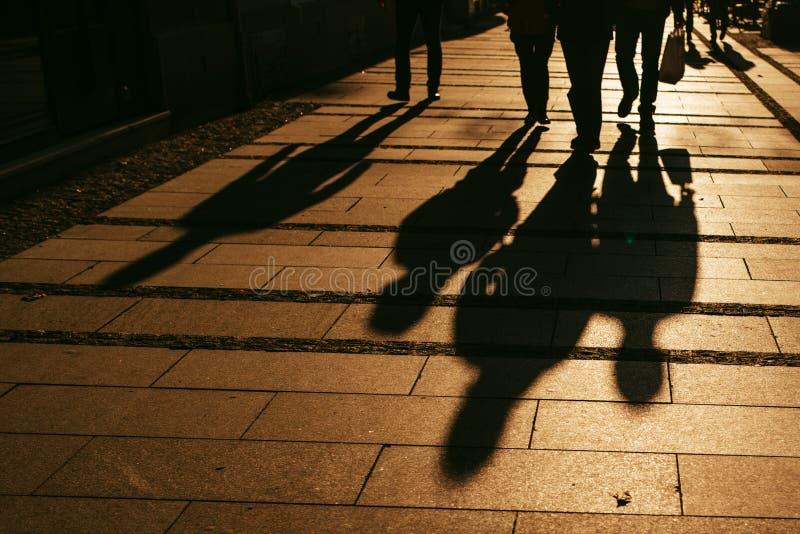 Силуэты людей идя на улицу города стоковые изображения rf