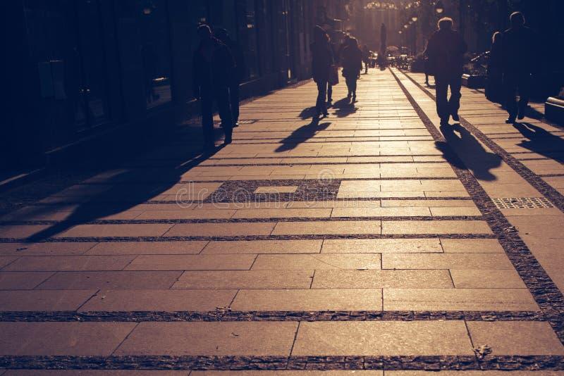 Силуэты людей идя на улицу города стоковое изображение rf