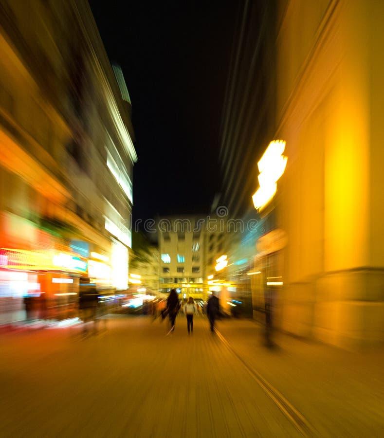 Силуэты людей на улицах города на ноче стоковые изображения