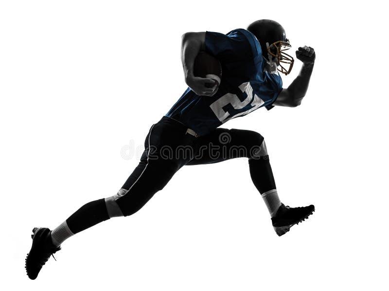 Силуэт американского человека футболиста идущий стоковое изображение rf