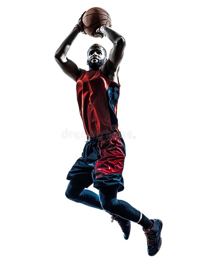 Силуэт африканского баскетболиста человека скача бросая стоковое фото