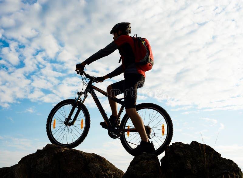 Силуэт велосипедиста с велосипедом на утесе на заходе солнца весьма спорты стоковая фотография rf