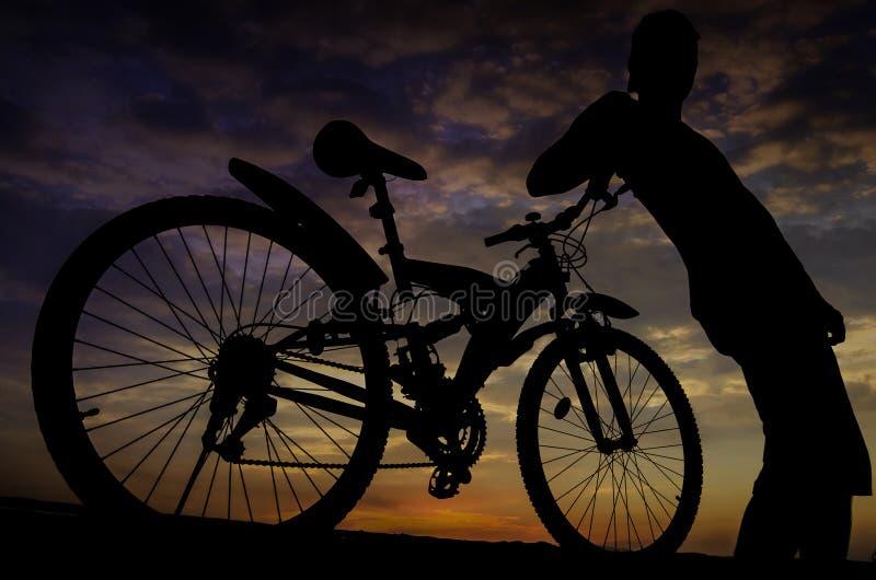 Силуэт велосипедиста с twilight небом стоковые изображения rf