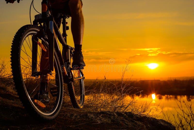 Силуэт велосипедиста Enduro ехать горный велосипед на скалистом следе на заходе солнца Активная принципиальная схема уклада жизни стоковое изображение rf
