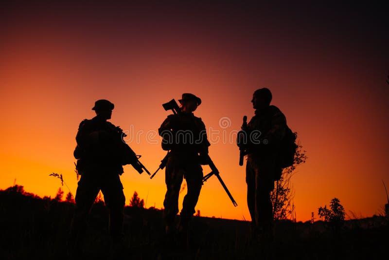 Силуэт воинских солдат с оружиями на ноче съемка, hol стоковые изображения rf