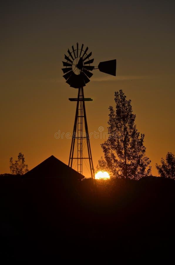 Силуэт восхода солнца мельницы и амбара ветра стоковая фотография