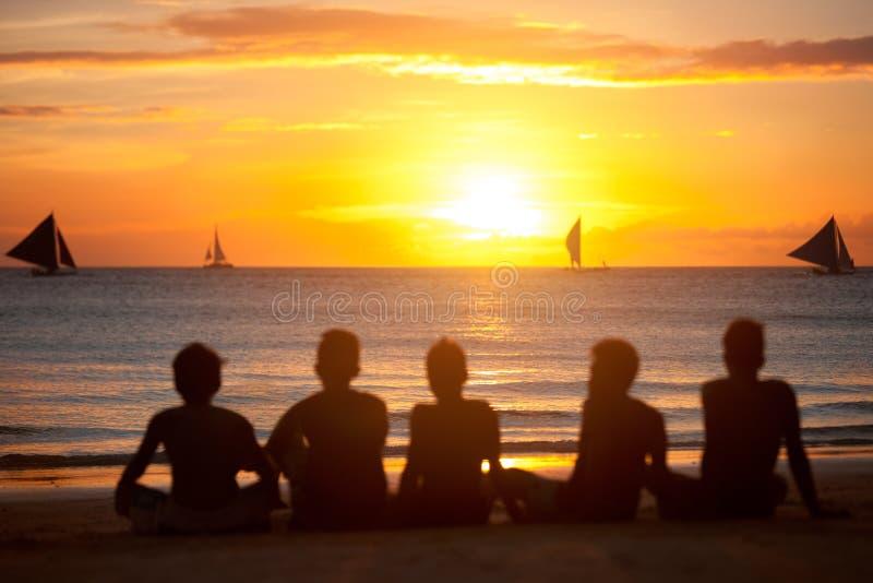 Силуэт группы в составе друзья в заходе солнца стоковые фотографии rf