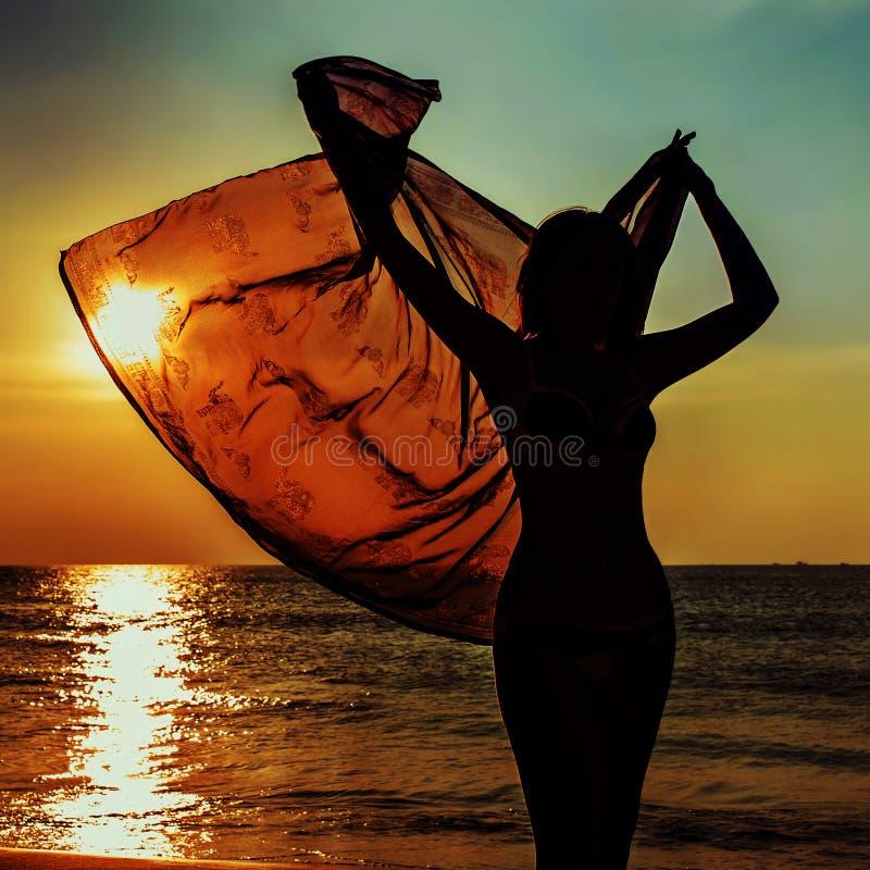 Download Силуэт девушки против моря захода солнца Стоковое Фото - изображение насчитывающей ткань, outdoors: 40575224