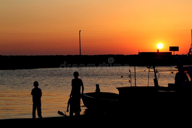 Силуэт детей в заходе солнца на пляже стоковое изображение rf