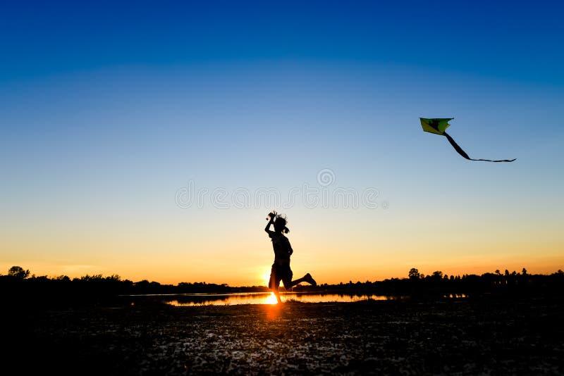 Силуэт детей летая змей на заход солнца стоковая фотография