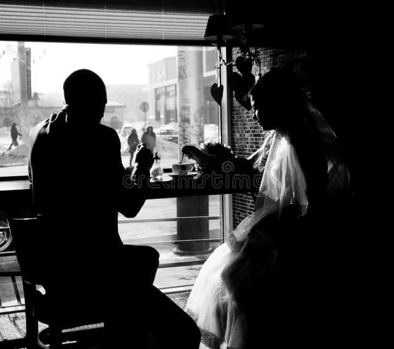 Силуэт жениха и невеста в кафе стоковые фото