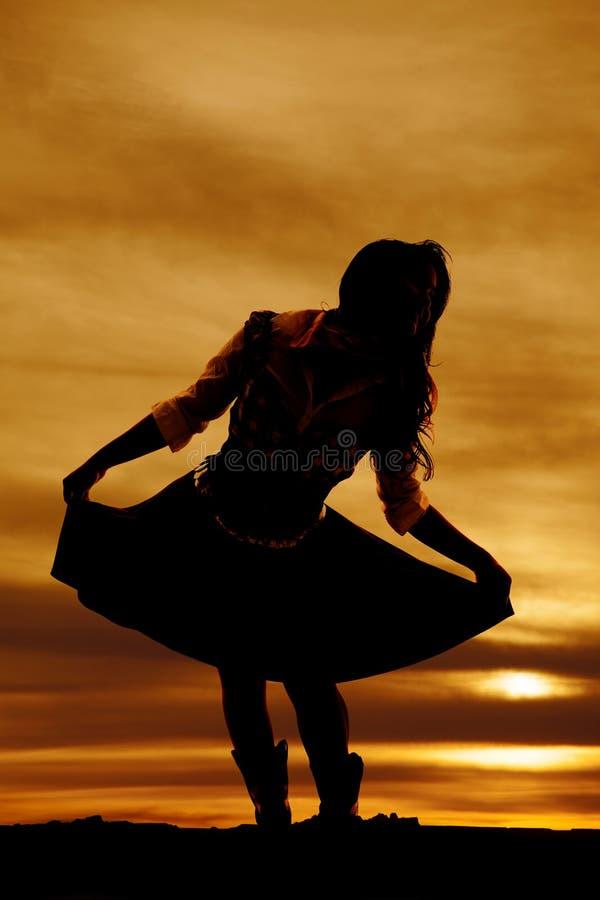 Силуэт женщины держа вне ее юбку полагаясь сверх стоковая фотография rf