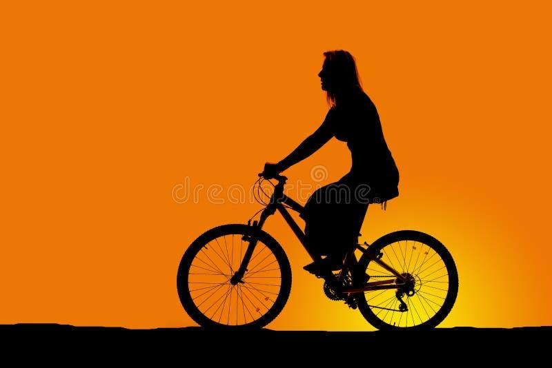 Силуэт женщины ехать велосипед стоковое изображение rf
