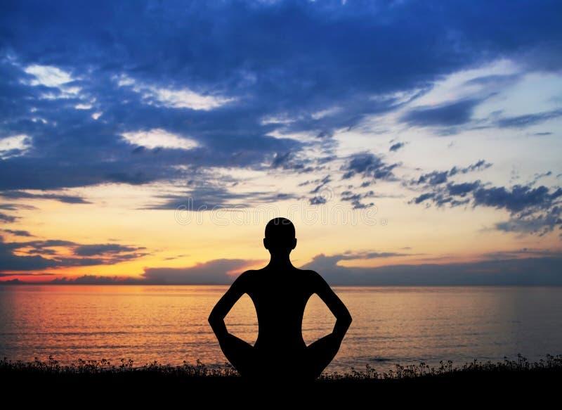 Силуэт женщины делая йогу на заходе солнца стоковые фотографии rf