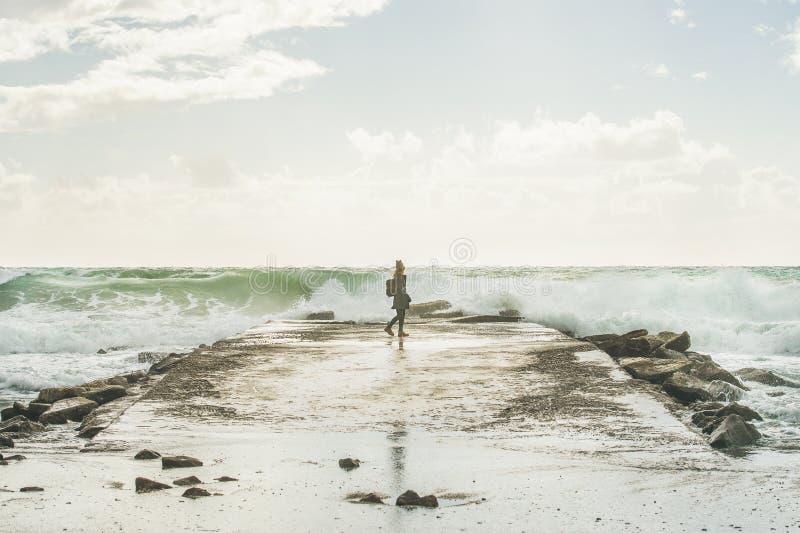 Силуэт женщины идя на пристань на бурном Средиземном море стоковые фото