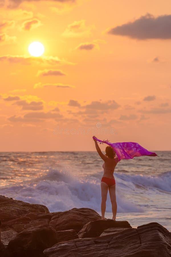 Силуэт женщины которая стоит против солнца захода солнца стоковое фото rf