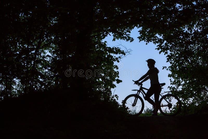 Силуэт женщины которая стоит с велосипедом стоковое изображение rf