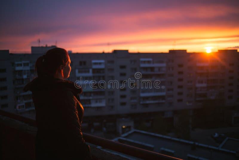Силуэт женщины наслаждаясь видом на город на заходе солнца Концепция одиночества, вечности, выбора стоковое фото rf
