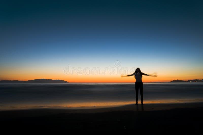 Силуэт женщины на пляже стоковое изображение rf