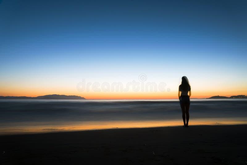 Силуэт женщины на пляже стоковые фотографии rf