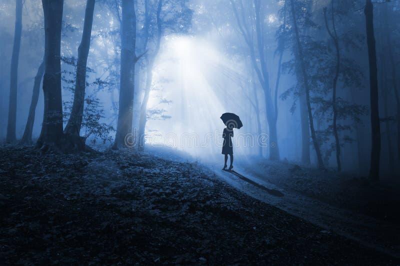 Женщины смотря на свет в темноте стоковые фото