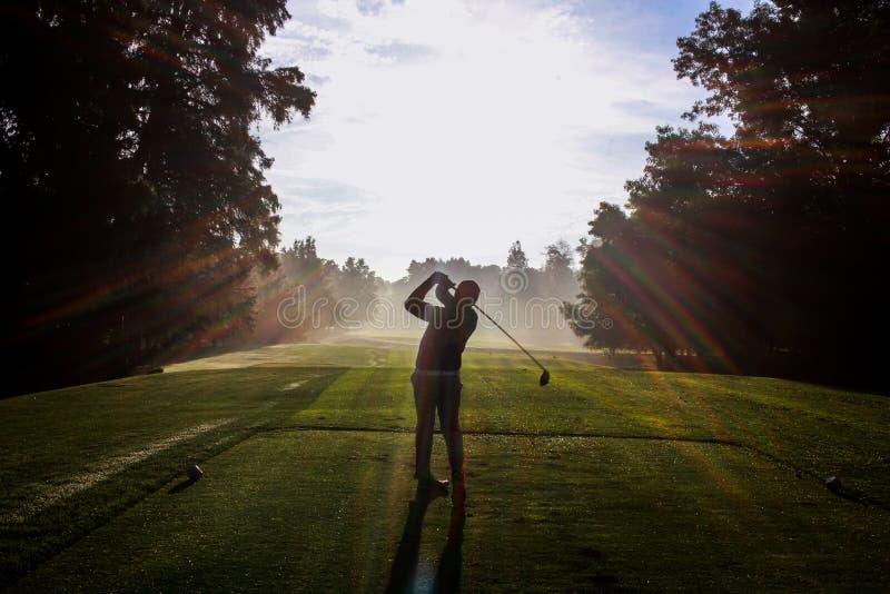 Силуэт игрока в гольф на зоре стоковая фотография
