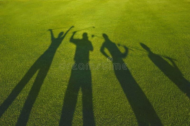 Силуэт 4 игроков в гольф на траве стоковая фотография rf