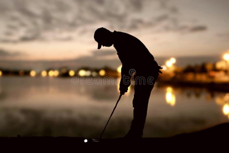 Силуэт игроков в гольф ударил подметать и держит поле для гольфа в заходе солнца стоковые изображения rf