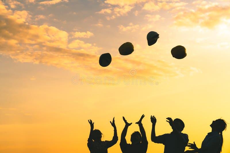 Силуэт инженеров по строительству и монтажу бросает шлем безопасности вверх на небе захода солнца, машиностроительной промышленно стоковая фотография