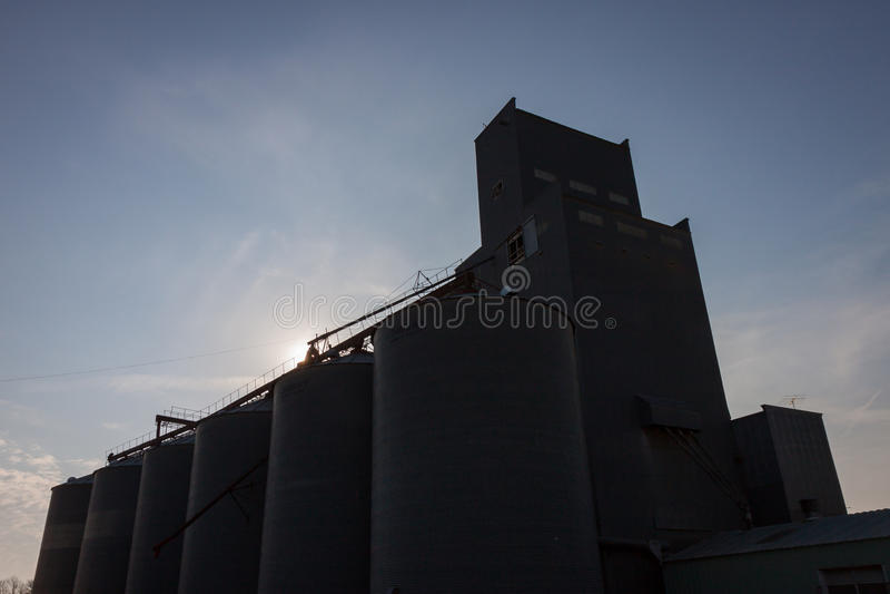 Силуэт лифта зерна против голубого неба стоковое фото